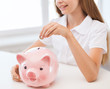smiling child putting coin into big piggy bank