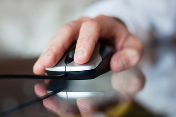close up of hand with computer mouse on blurred background