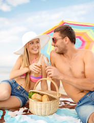 smiling couple having picnic on the beach