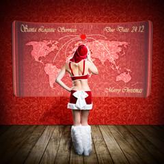 Weihnachtsfrau steht vor Display mit Weltkarte