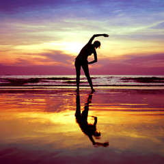 Silhouette of young woman, yoga stretching exercises