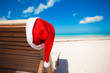 Santa hat on chair longue at tropical caribbean beach
