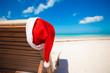 Santa hat on chair longue at tropical caribbean beach