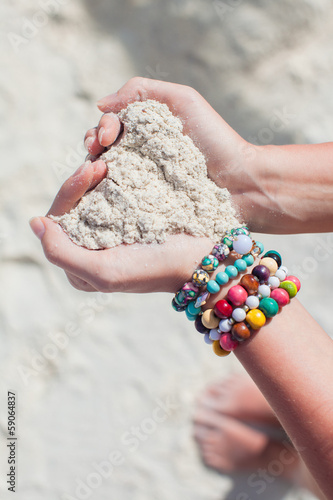 Close-up of sand heart in woman's hands decorated with colorful