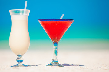 Two cocktails: pina colada and strawberry margarita on white