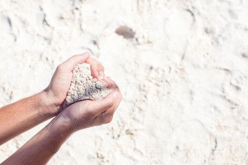 Close-up of sand heart in man's hands
