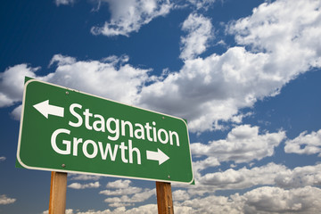 Stagnation or Growth Green Road Sign Over Clouds and Sky