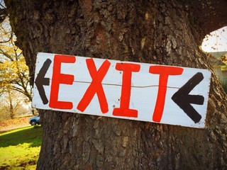 Exit Sign in White Red and Black on Tree