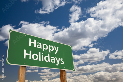 Happy Holidays Green Road Sign Over Clouds and Sky