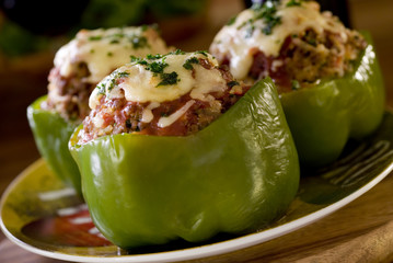 Closeup of three stuffed green bell peppers.