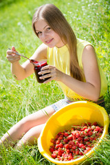 Young happy teen girl eating strawberry jam