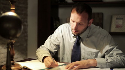 Young tired accountant working late with documents at his office