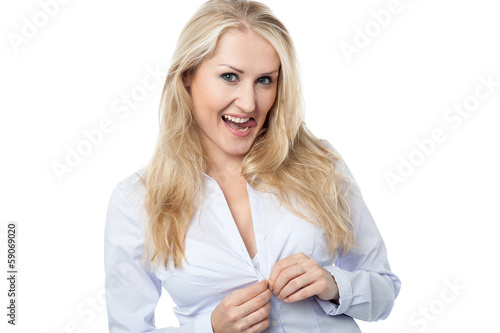 Young woman buttoning her shirt