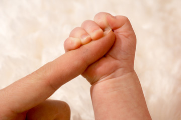 Baby hand grasping the finger of the mother
