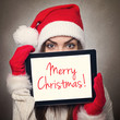 Cute young woman hiding behind tablet computer wearing Santa hat