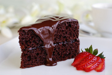Piece of chocolate cake with warm fudge sauce.