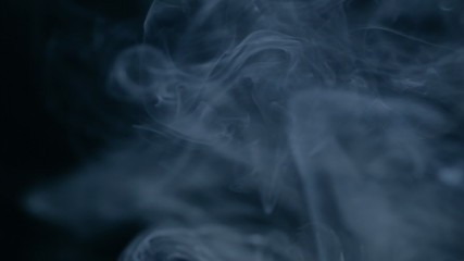 Smoke slow floating in space against black background