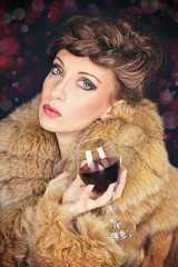 Elegant lady in fur coat celebrating Christmas drinking wine