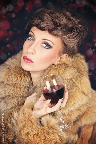 Elegant lady in fur coat celebrating Christmas drinking wine