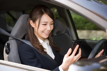 車でスマートフォンを見る女性 ビジネス