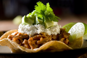 tostada topped with shredded pork, feta and vegetables.