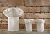 Three chef;s toques on brick wall