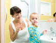 mother and baby brushing teeth in bathroom