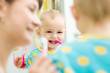 mother teaches baby brushing teeth