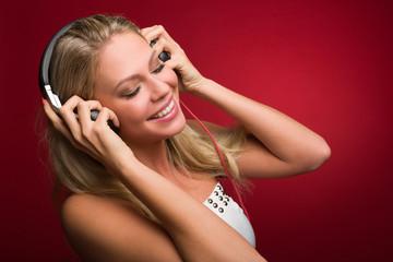 Blonde Frau genießt die Musik aus Kopfhörern