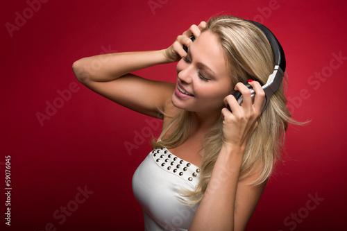 canvas print picture Blonde Frau genießt die Musik aus Kopfhörern