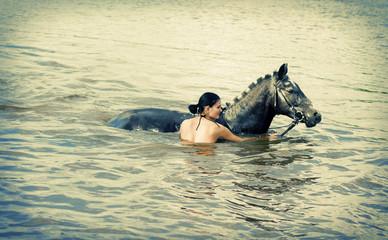 woman swimming winth her black stallion