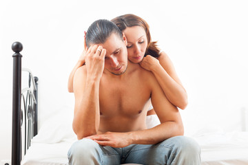 Man has sad face, woman consoling him on bed in bedroom