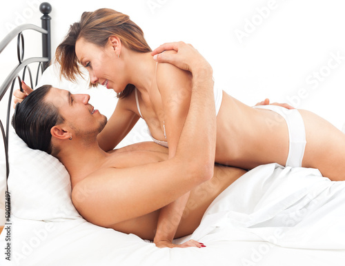 Smiling adult couple having sex on bed in bedroom interior