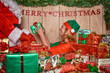 Elf puttings presents in Santa's sack