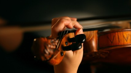 Woman playing violin over dark background