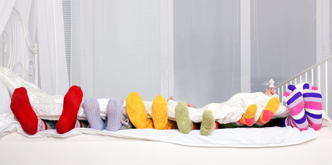 Happy family in colorful socks on white bed.