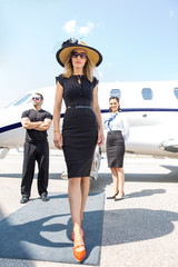 Beautiful Woman With Bodyguard And Airhostess Against Private Pl