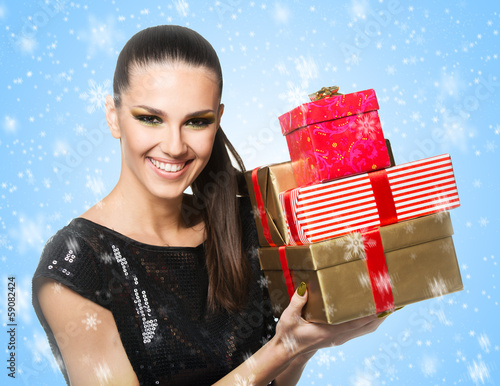 Beautiful woman holding presents over a snowy background