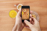 Hands taking photo of breakfast with smartphone
