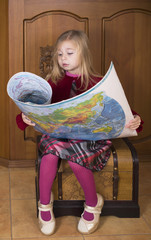little girl sits on a chest and considers world map close up