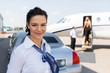 Beautiful Airhostess Standing Against Limousine And Private Jet