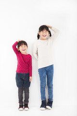 happy children stand before white wall