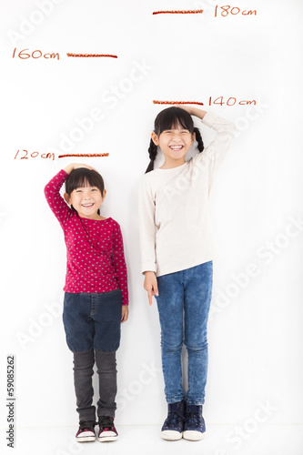 Happy little girls growing up and against the wall