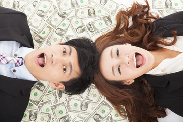 surprised businessman and woman lying on the money