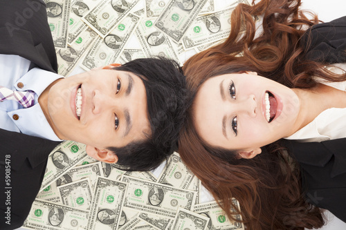 happy businessman and woman lying on the money