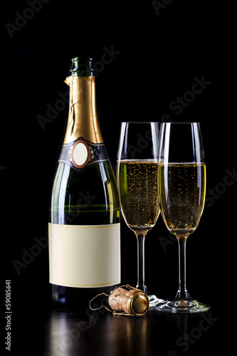 champagne bottle and two glasses on black background