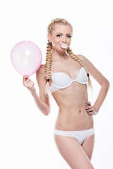Beautiful blond girl posing with pink balloon and bubble gum.
