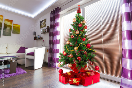 Beautiful Christmas tree with presents in modern apartment