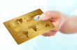 gold credit card holded by hand over white