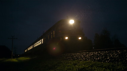 Train passing fast through a rural area, by night